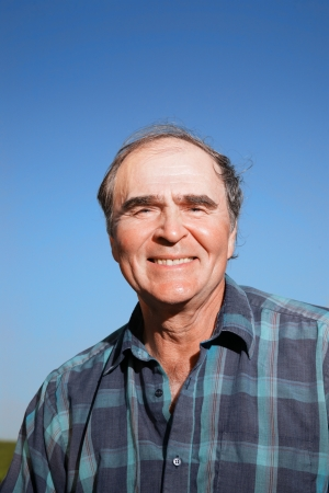 Portrait of a happy senior man outdoors over blue sky. photo