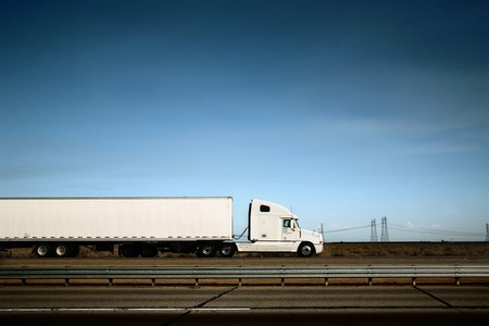 moving truck: White freight truck driving on freeway under blue sky. Stock Photo