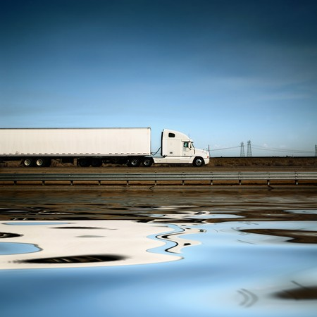 White freight truck driving on freeway under blue sky. Stock Photo