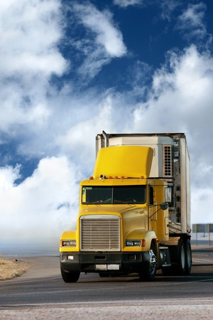 delivery truck: Big yellow trailer on the road over dramatic blue sky with white clouds.