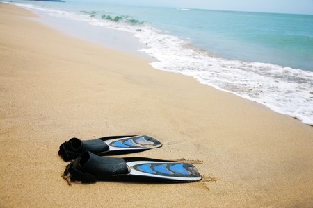 Pair of swimfins on the sand at ocean water Banco de Imagens