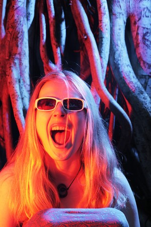 Young woman screaming in colorful dramatic light photo