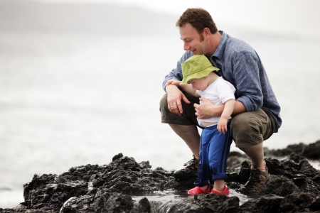 Dad with little son walking outdoors at ocean photo