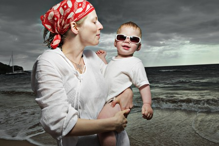 Mother and son at the ocean at sunset photo