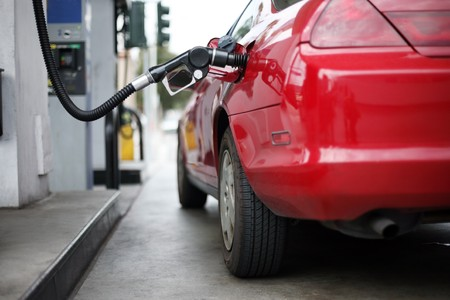 benzine: Red car at gas station being filled with fuel. Shallow DOF. Stock Photo