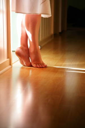 laminate flooring: Female legs standing on toes on hardwood floor