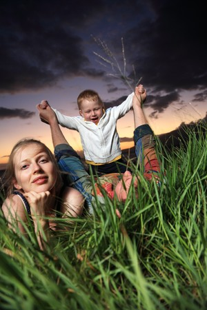 Young family lying in green grass over scenic sunset. photo
