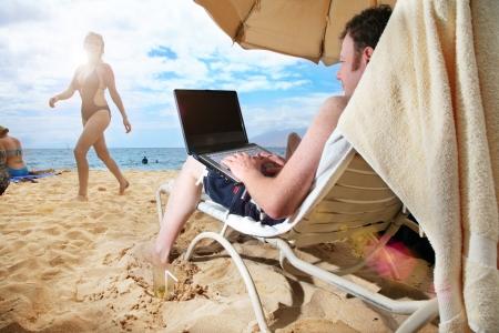 하와이 열 대 해변에서 랩톱에서 작업하는 사람 스톡 콘텐츠