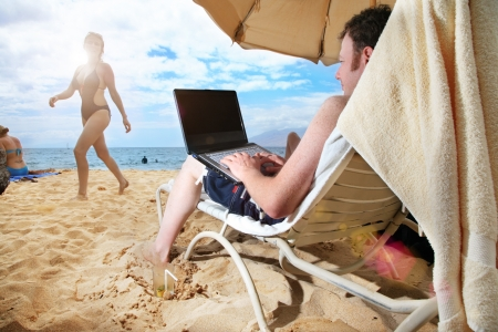 Man working on laptop at tropical beach in Hawaii photo