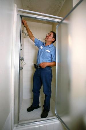 cabine de douche: Handyman en chemise bleue fixation douche Banque d'images