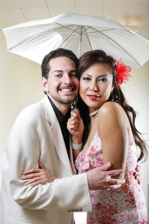 Happy smiling young couple hugging under white umbrella photo