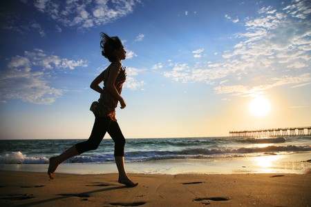 Girl at the beach running by the ocean at sunset photo