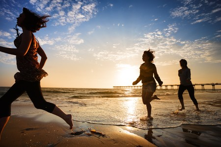 Three girls at the beach running by the ocean at sunset Stock Photo
