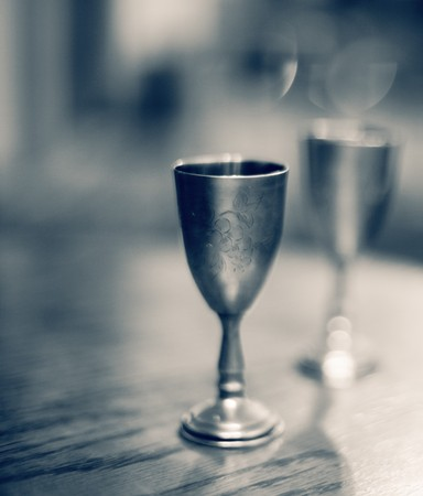 metal: Two vintage metal wine glasses on table. High grain effect, shallow DOF. Stock Photo