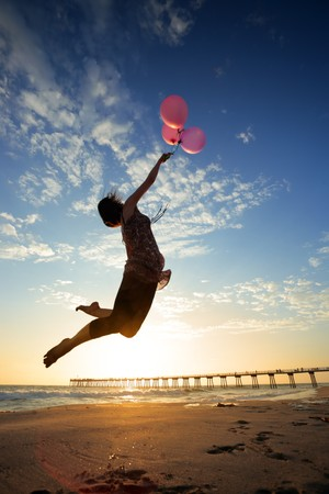 Girl flying with balloons at sunset beach photo