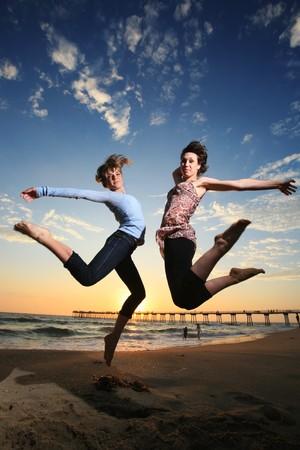 Twee meisjes springen op het strand bij zonsondergang