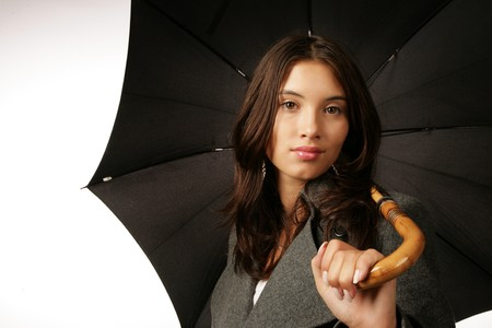 Beautiful young woman with black umbrella over white background Stock Photo - 4319872