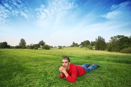Man lying on green grass in beautiful landscape photo