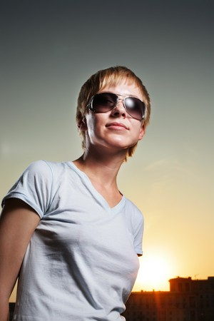 Portrait of cool young woman in sunglasses at sunset photo