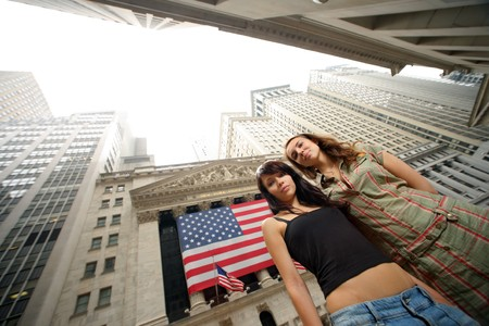 stock: Two young women near New York Stock Exchange. WIde angle portrait.