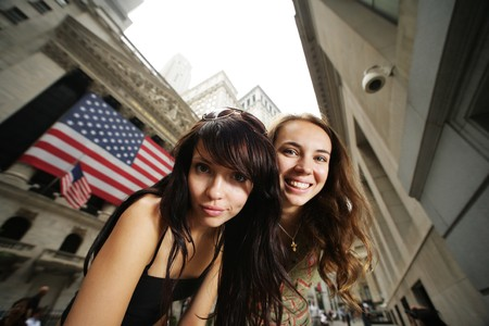 outdoor photo: Two young women near New York Stock Exchange. WIde angle portrait.