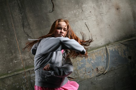 fighting styles: Young woman throwing a pinch on a dark street