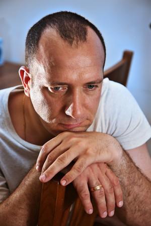 Sad man thinking with head on hands photo