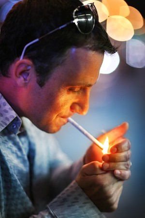 man profile: Man lighting a cigarette. Shallow DOF.