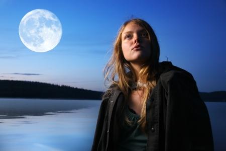 noche y luna: Joven y bella mujer en la noche al aire libre en el lago Foto de archivo