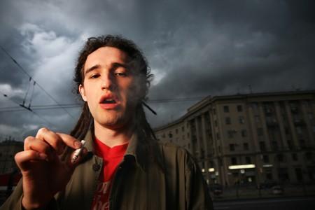 Man with dreadlocks smoking on street Stock Photo - 4319953