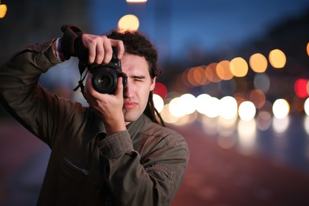 picture person: Photographer taking photo with DSLR camera at night. Shallow DOF. Stock Photo