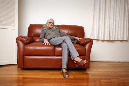 crossed legs: Senior woman sitting on leather sofa at home