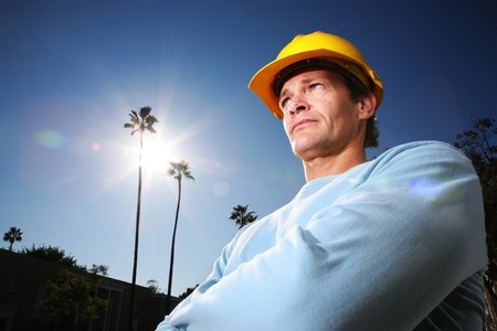 hard: Construction worker in yellow hard hat over blue sunny sky
