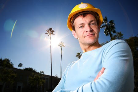 Construction worker in yellow hard hat over blue sunny sky photo