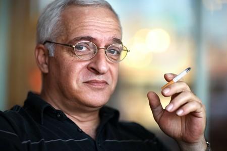 Elderly man smoking cigarette. Shallow DOF, focus on eye. Stock Photo - 4319945