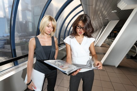 asian architect: Two businesswomen looking into folder in futuristic interior
