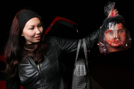 Woman holding dummy bloody male head in plastic bag at night.