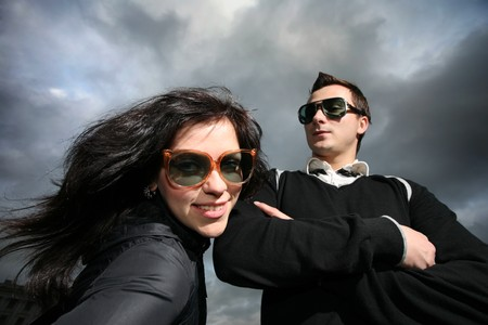 proportions of man: Cool young couple over dramatic cloudy sky Stock Photo