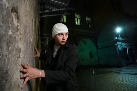 Young man leaning to a wall on night street Stock Photo