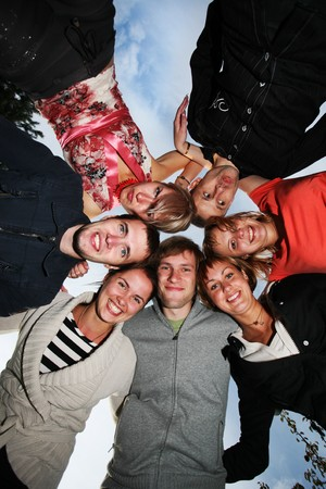 Group of happy young people in circle outdoors Stock Photo