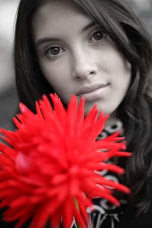 Beautiful woman with red flower. Close-up, shallow DOF, focus on eyes. Stok Fotoğraf