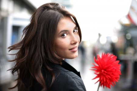 turn: Beautiful woman with red flower walking down street, looking back. Shallow DOF.