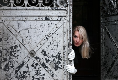 Beautiful woman looking looking out of dark vintage gate Stock Photo - 4320098