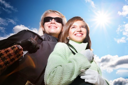 Two young beautiful women over blue sunny sky at autumn or winter. photo