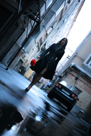 Beautiful woman walking in rainy autumn city