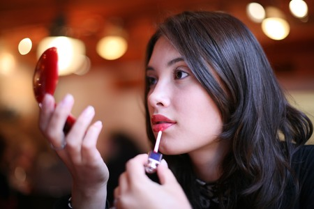 Beautiful young woman painting lips in red color. Shallow DOF. photo
