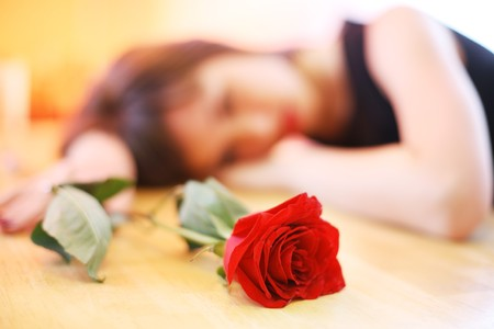 woman sad: Lonely joven con rosa roja. Someras DOF, se centran en flor.