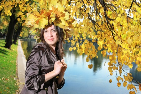 Beautiful young woman in crown of golden autumn leaves in park. photo