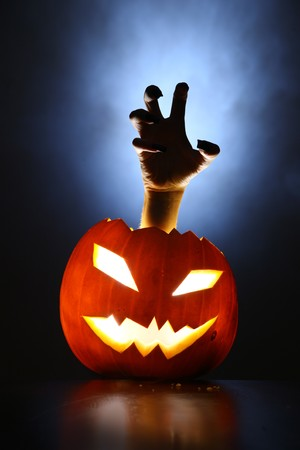Hand of horror raising from glowing pupmkin lantern. Stock Photo - 4322033