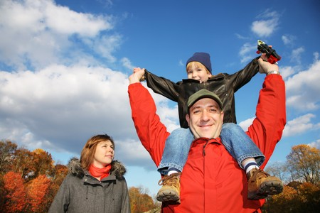 Young family in autumn park. Father holding his son on his shoulders against blue sky. photo